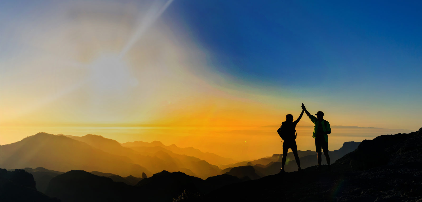 Two people, on top of a mountain high-five as they look into a sunset